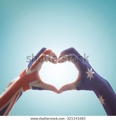 Happy labour day: Australia flag pattern on people hands in heart shaped form on vintage style color tone sky background: Australia national public holiday celebration symbolic concept design idea     - stock photo