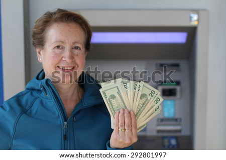 Happy lady showing her money at an ATM - stock photo