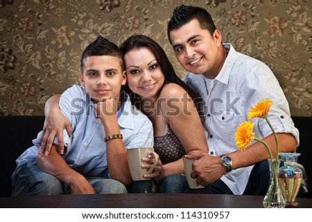 Happy Latino family hugging each other indoors - stock photo