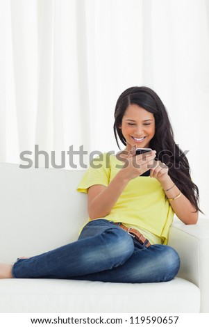 Happy Latino looking her smartphone while sitting on a sofa - stock photo