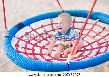 Happy laughing baby, adorable little boy enjoying a swing ride having fun on a playground in summer - stock photo