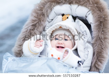 Happy laughing baby girl enjoying a walk in a snowy winter park sitting in a warm stroller with sheepskin hood - stock photo