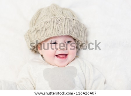 Happy laughing baby in a knitted hat - stock photo