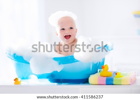 Happy laughing baby taking a bath playing with foam bubbles. Little child in a bathtub. Smiling kid in bathroom with colorful toy duck. Infant washing and bathing. Hygiene and care for young children. - stock photo