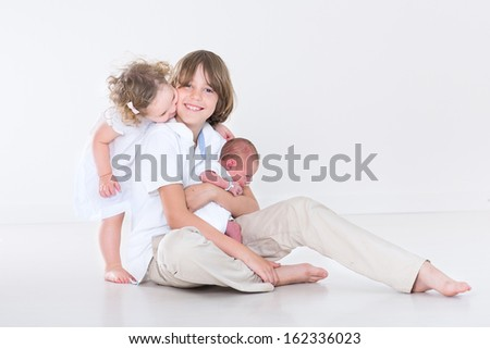 Happy laughing boy and his adorable toddler sister playing with their newborn baby brother - stock photo