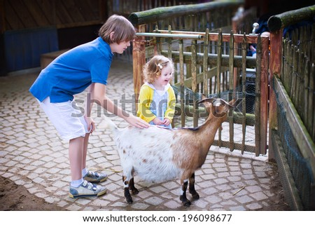 Happy laughing boy and his little toddler sister, adorable curly girl, playing together petting a goat laughing and having fun watching animals on a day trip to a modern city zoo - stock photo