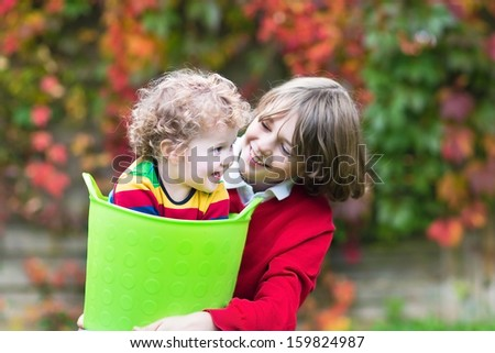 Happy laughing brother and baby sister playing together in the garden with a laundry basket - stock photo