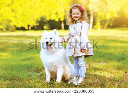 Happy laughing child and dog having fun outdoors in warm autumn day - stock photo