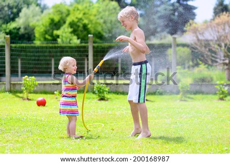 Happy laughing children, young school boy and his adorable toddler sister, enjoying hot sunny summer vacation day playing outdoors in garden at the backyard of the house spraying water from the hose - stock photo