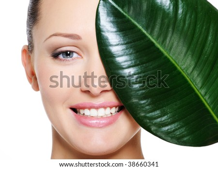 Happy laughing face of woman and large green leaf over white background - stock photo