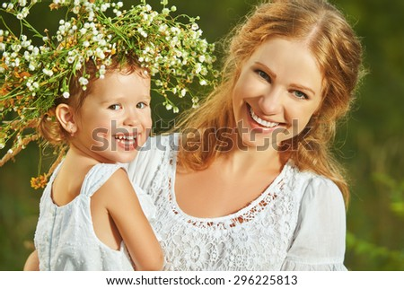 happy laughing family, daughter hugging mother in wreaths of summer flowers in nature - stock photo