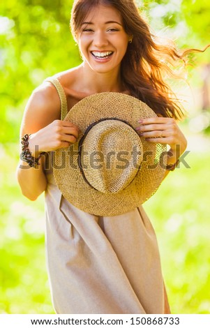 happy laughing girl holding straw walking in the green summer park - stock photo