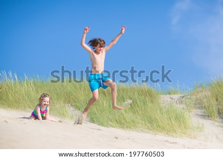 Happy laughing kids, school age boy and funny curly toddler girl, brother and sister, playing on a beach,jumping in sand dunes enjoying vacation on a sunny summer day on North Sea, Holland - stock photo