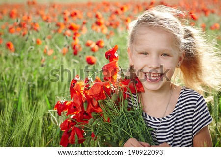 Happy laughing little girl standing on the poppy meadow and holding a posy - stock photo