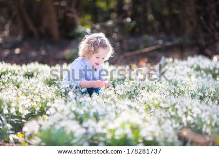 Happy laughing toddler girl playing with first spring flowers in a beautiful spring sunny park - stock photo