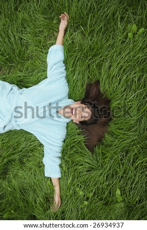Happy laughing woman lying wide arms in green grass - stock photo
