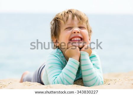 Happy laughing 4 year girl laying on sand beach - stock photo