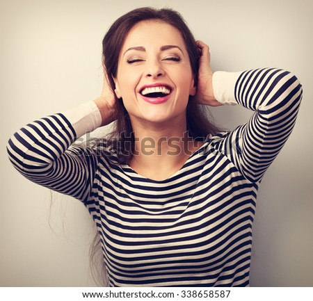 Happy laughing young casual woman with closed eyes holding the head. Vintage closeup portrait - stock photo