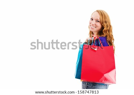 happy laughing young redhead woman with shopping bags on white background - stock photo