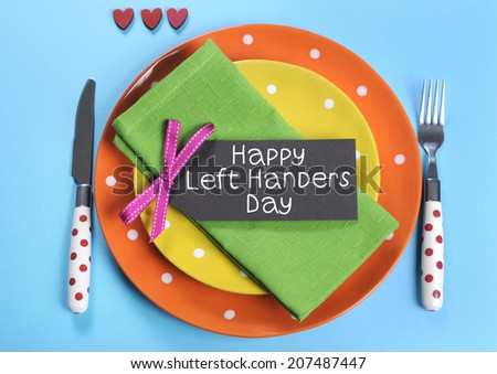 Happy Lefthanders Day, for August 13, International Left-handers Day, with colorful table setting showing reverse cutlery placing, in orange, yellow, pale blue and green polka dot colors. - stock photo