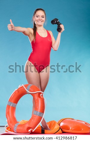 Happy lifeguard with ring buoy lifebuoy and binoculars. Woman girl supervising swimming pool water on blue. Accident prevention. - stock photo