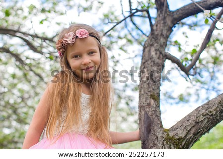 Happy little adorable girl in blossoming apple tree garden - stock photo
