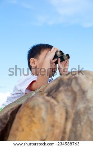 Happy little asian boy exploring outdoors prone on a boulder with telescope, young boy using binoculars to view the front, bright sky background - stock photo