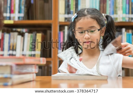 Happy little asian child girl w/ eyeglasses reading book school background: Lovely cute young female student kid opening flipping book in archive resource collection room: National library lover month - stock photo