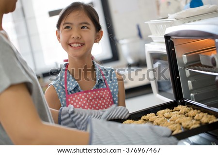 Happy little Asian cute chef looking cookies from oven - stock photo