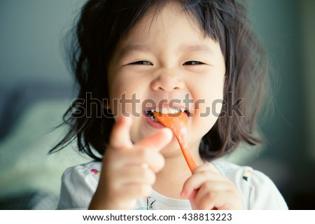 Happy Little asian girl eating yogurt and she have spoon in her mouth. - stock photo