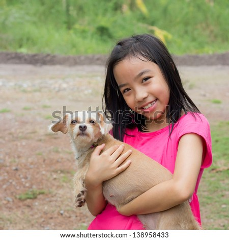 happy little asian girl hugging her pet - stock photo