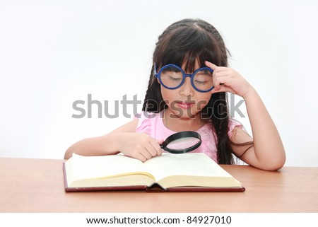 Happy little asian girl reading book wearing blue glasses, back to school concept, isolated over white - stock photo