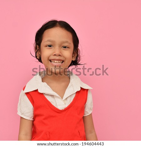 Happy little asian girl standing and smiling. - stock photo