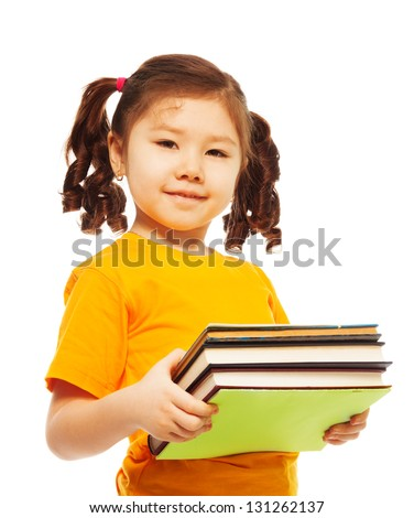 Happy little Asian girl with ponytails holding pile of books and smile, standing isolated on white - stock photo