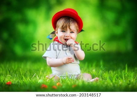 Happy little baby in red hat having fun in the park on solar glade. Summer vacations concept. The emotions. - stock photo