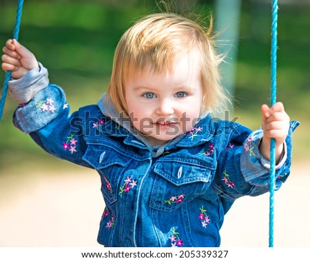 happy little baby on swing outside - stock photo