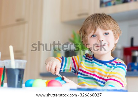 Happy little blond kid boy coloring eggs for Easter holiday in domestic kitchen, indoors. Child having fun and celebrating feast. - stock photo