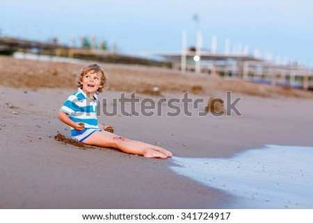 Happy little blond kid boy having fun with building sand castle on the beach of ocean or see by sunset. Funny child spending active vacations. - stock photo