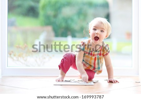 Happy little blonde toddler girl playing with puzzles sitting on the tiles floor next to a big window - stock photo