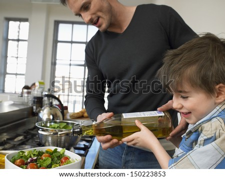 Happy little boy and father preparing salad together in kitchen - stock photo