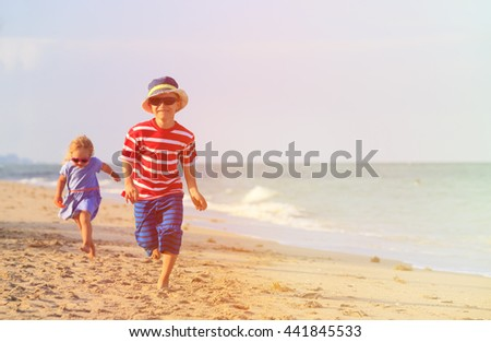 happy little boy and girl running on sand beach - stock photo