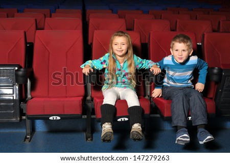 Happy little boy and girl together watching a movie  - stock photo