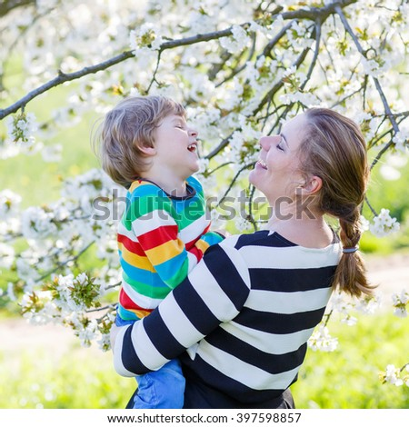 Happy little boy and his mother hugging in blooming cherry garden in spring. Happy family celebrating mother's day. - stock photo