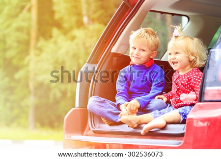 happy little boy and toddler girl travel by car - stock photo