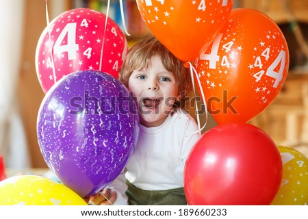Happy little boy celebrating his 4 birthday with colorful balloons, indoor in kids room. - stock photo