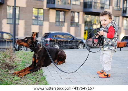Happy little boy child and Doberman dog l together  in the city park  park - stock photo