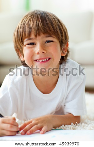 Happy little boy drawing lying on the floor in the living-room - stock photo