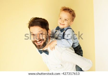 Happy little boy enjoying with riding on father's back - stock photo