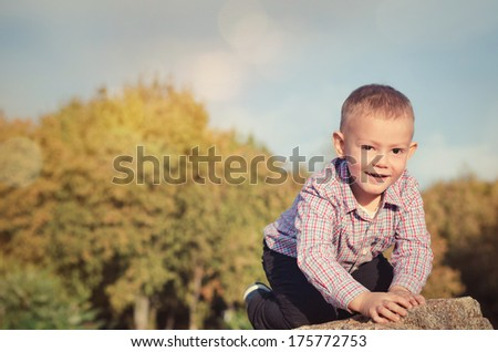 Happy little boy exploring outdoors clambering over a rock with a beautiful smile on his face with copyspace - stock photo