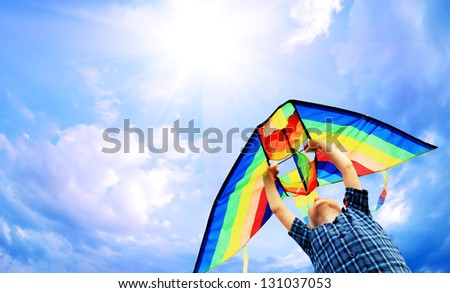 Happy little boy flies a kite in the sunny sky - stock photo
